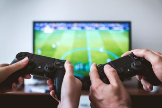 Image of two hands holding game console infront of tv screen.